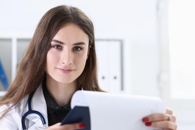 Linda médica sorridente segura a almofada da área de transferência e preenche algo com caneta prata. a prevenção de doenças físicas prescreve a ala de remédios em volta do conceito de estilo de vida saudável