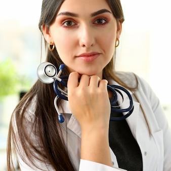 Linda médica sorridente sente-se no local de trabalho