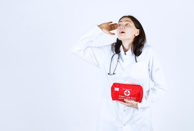 Linda médica tapando a boca com a mão enquanto fica horrorizada e segura sua maleta médica