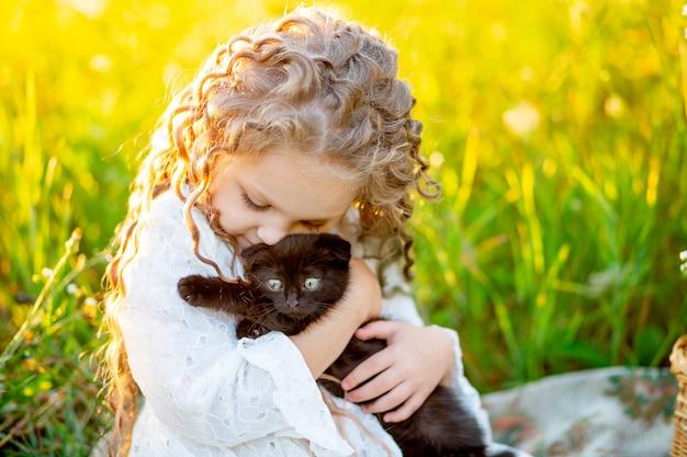 Linda menina abraça um gatinho preto no gramado no verão