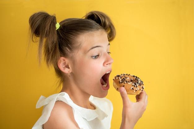 Linda menina adolescente comendo uma rosquinha.