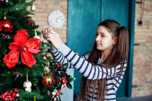 Linda menina adolescente decora a árvore de natal em casa. Foto Premium