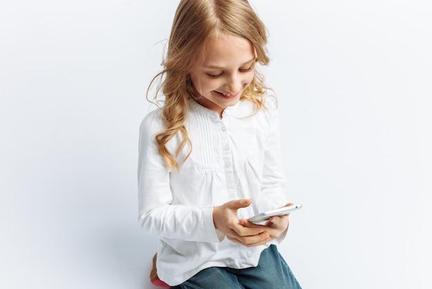 Linda menina adolescente olhando para o telefone, falando em vídeo