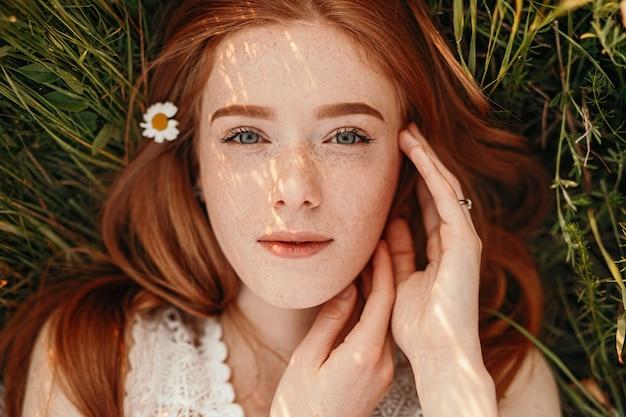 Linda menina adolescente ruiva tranquila deitada na grama