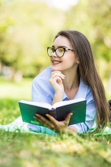 Linda menina adolescente sonhadora deitada na grama do parque da cidade com caneta e caderno