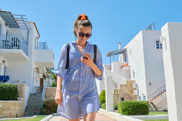 Linda menina adolescente sorridente andando usando smartphone