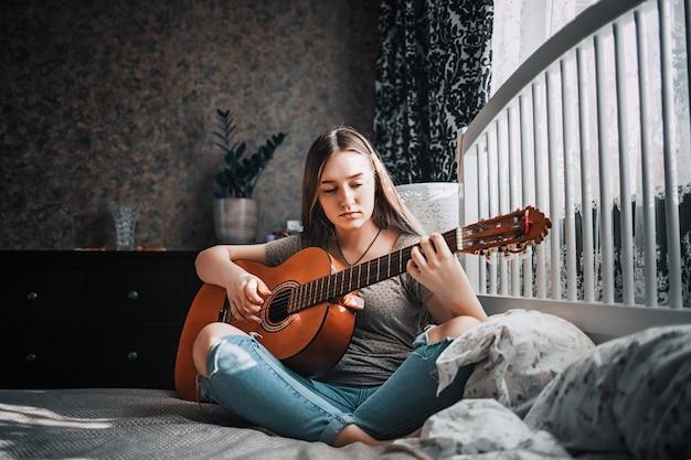 Linda menina adolescente tocando guitarra no quarto dela.