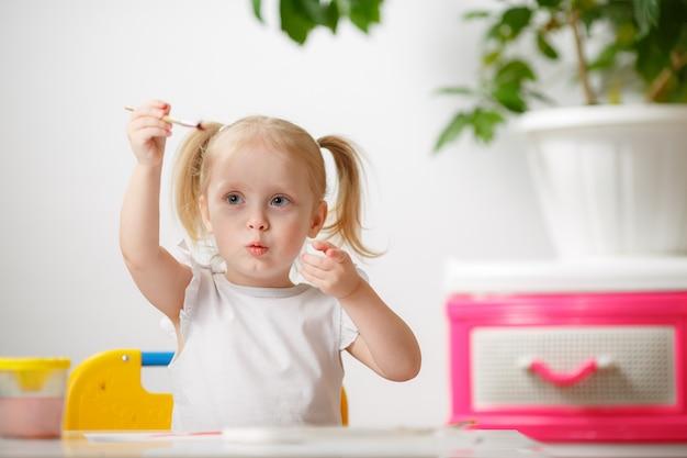 Linda menina adorável aprendendo pintura com aquarela. criança pequena desenho em casa, usando pincéis coloridos. filha feliz e saudável experimentando cores, água em casa ou no berçário