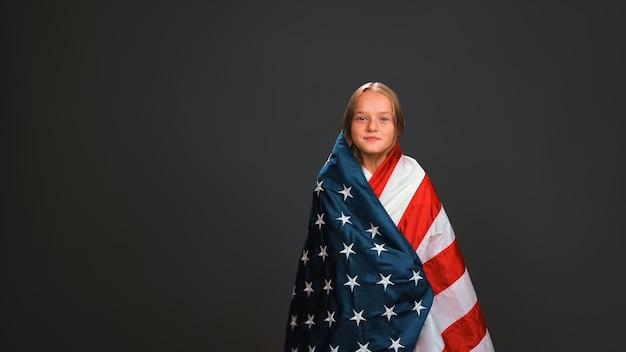 Linda menina adorável envolta em uma bandeira dos eua celebra o dia da independência e expressa patriotismo isolado na parede preta