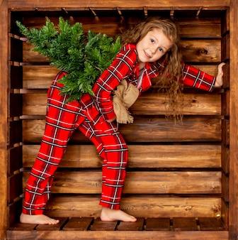 Linda menina alegre em um pijama de natal xadrez vermelho com uma pequena árvore de natal nas mãos em um fundo de madeira