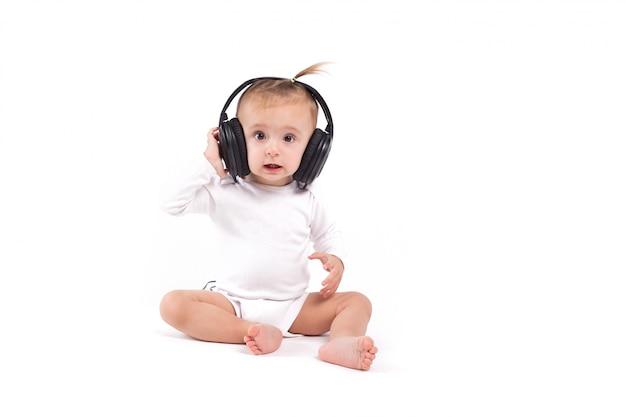 Linda menina alegre na camisa branca e fones de ouvido na cabeça