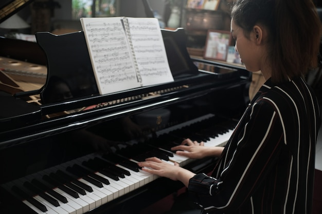 Linda menina asiática aprender a tocar piano.