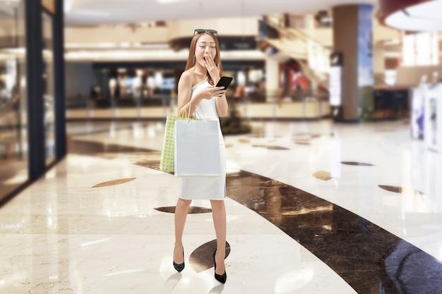Linda menina asiática com telefone móvel carregando sacolas de compras andando