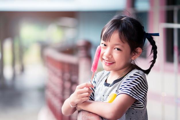 Linda menina asiática come sorvete no verão em casa