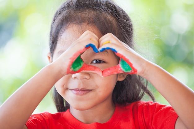 Linda menina asiática criança pequena com as mãos pintadas fazem formato de coração colorido