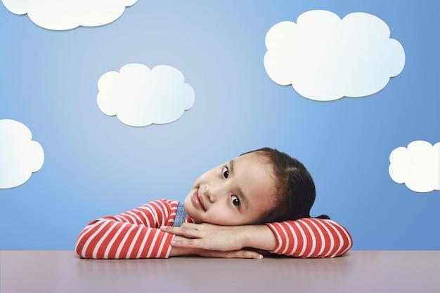 Linda menina asiática deitada na mesa