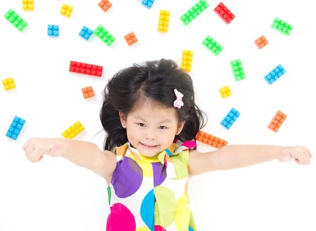 Linda menina asiática deitada no chão, brincando com blocos coloridos