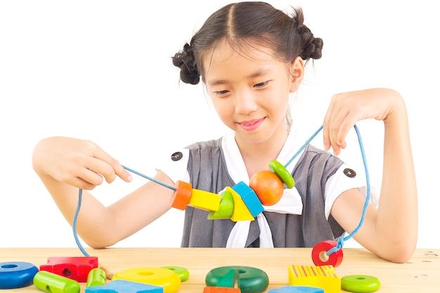 Linda menina asiática é jogar brinquedo colorido bloco de madeira