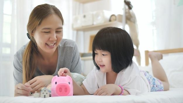 Linda menina asiática e mãe colocando dinheiro no cofrinho para salvar