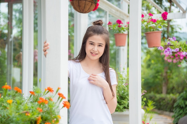 Linda menina asiática em pé no parque e sorri para a câmera