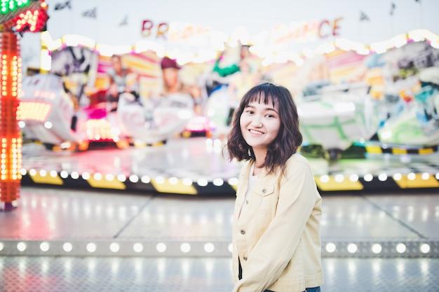 Linda menina asiática em um parque de diversões, sorrindo