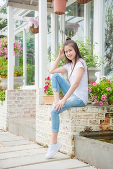 Linda menina asiática sentado em frente a sua casa e sorrisos