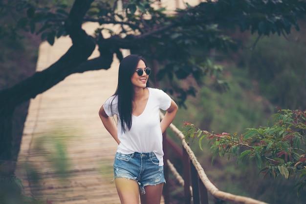 Linda menina asiática sorri no jardim, conceito de natureza ao ar livre