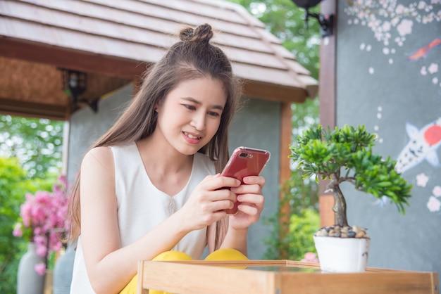 Linda menina asiática usando smartphone e sorrisos em casa