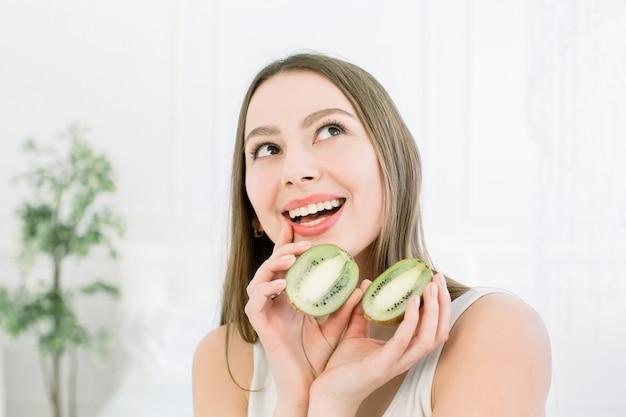 Linda menina bonita, segurando uma fatia de kiwi perto da cabeça e sorrindo. alimentos saudáveis para a pele fresca. conceito de beleza