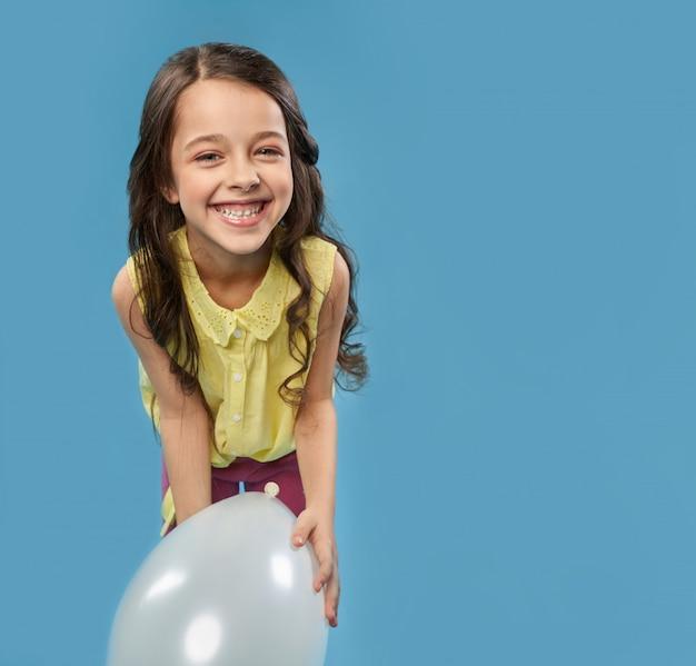 Linda menina brincando com balão e relaxante