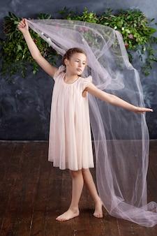 Linda menina brincando com um tecido leve contra as flores. retrato da menina simpática. menina dançante.