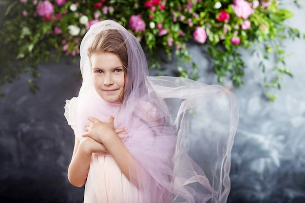 Linda menina brincando com um tecido leve contra as flores. retrato da menina simpática.
