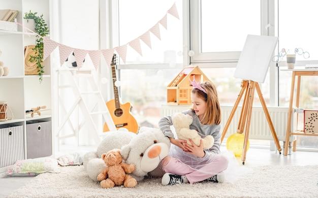 Linda menina brincando com ursinhos de pelúcia em um lindo quarto