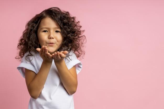Linda menina caucasiana com penteado encaracolado em camiseta branca, mandando beijo do ar nas palmas das mãos, expressando amor, isolado