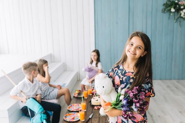 Linda menina com brinquedo e flores na festa de aniversário