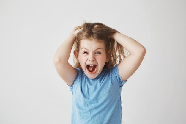 Linda menina com cabelo claro, gritando alto, segurando o cabelo com as mãos, estar assustada com uma grande aranha na parede do quarto.