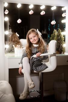 Linda menina com cabelo encaracolado em um salão de beleza no contexto de um grande espelho.