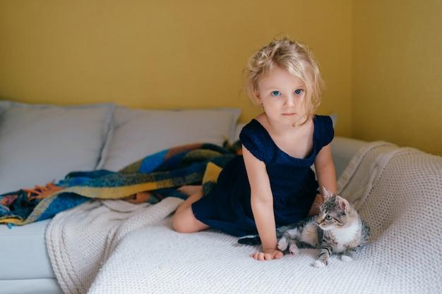 Linda menina com cabelo loiro senta-se em um sofá e brinca com seu gato.