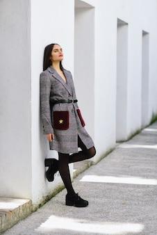 Linda menina com cabelo muito comprido, vestindo casaco de inverno, sentado no chão de um parque urbano