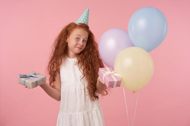 Linda menina com cabelo ruivo cacheado, vestido branco e boné de aniversário feliz olhando para a câmera com alegria, segurando caixas de presente nas mãos, em pé sobre um fundo rosa e balões coloridos