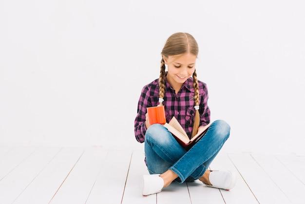Linda menina com caneca, lendo um livro