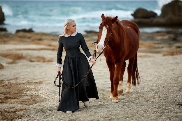 Linda menina com cavalo no litoral