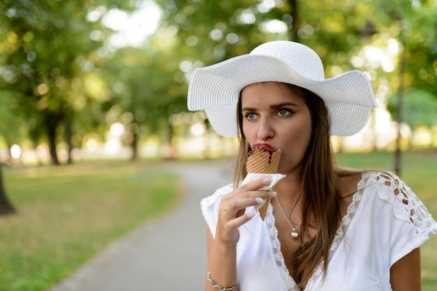 Linda menina com chapéu branco comendo sorvete na rua da cidade