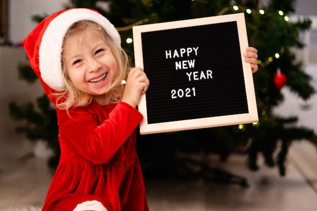 Linda menina com chapéu de papai noel e vestido de natal vermelho está deitada sob a árvore de natal e rindo, ao lado de um quadro preto e um texto com letras brancas feliz ano novo 2021. foto de alta qualidade