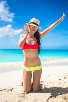 Linda menina com concha nas mãos na praia tropical