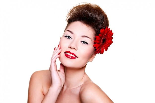 Linda menina com flor de lábios vermelhos no cabelo