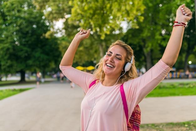 Linda menina com fones de ouvido, aproveitando seu tempo