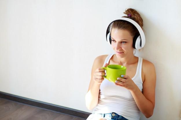 Linda menina com fones de ouvido, ouvindo música e bebendo café