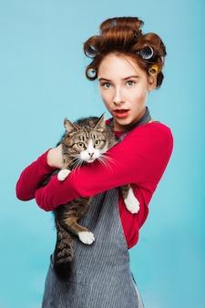 Linda menina com gato bonito nas mãos, posando e olhando