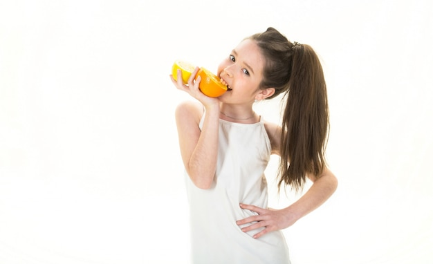 Linda menina com laranjas, limões, toranjas, vitamina. menina segurando uma laranja grande e suculenta.